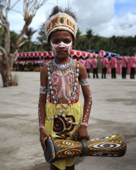 """A boy from a Papuan tribe holding a traditional drum known as """"tiba"""" during the Lake Sentani festival."""