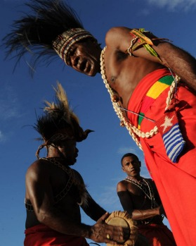 Papuan tribesmen crowned with preserved plumes of Birds of Paradise feathers as they participate in the Lake Sentani ...