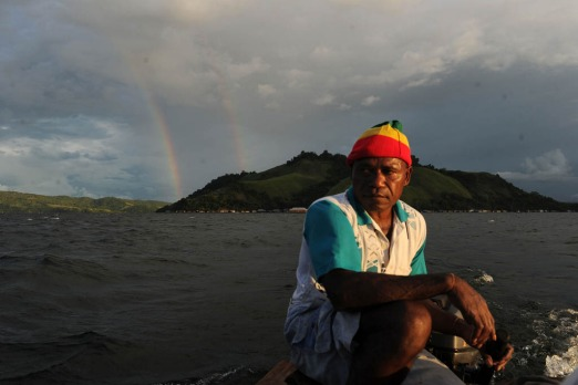 A double rainbow casts near the island as Papuan tribesman Yoseph Taime, travels on Lake Sentani, the site of annual ...