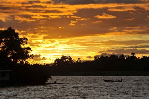 Sunset glows while a boat of Papuan tribesmen travel on Lake Sentani, the site of annual festival located in Indonesia's ...