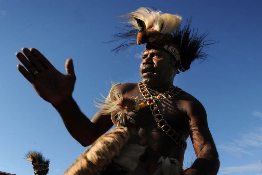 Papuan tribesman crowned with a preserved plume of a Bird of Paradise participate in the Lake Sentani festival.
