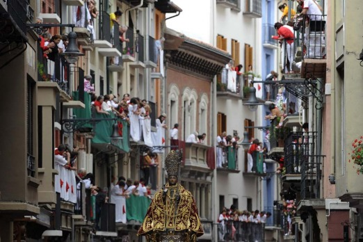 People watch from balconies as the statue of San Fermin, patron saint of the San Fermin festival, is carried through the ...