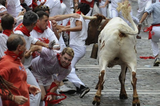 A steer pushes a reveller with his horn during the first bull run.