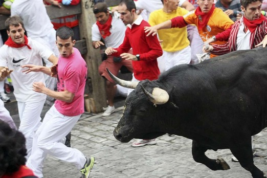 Fear on the faces of runners as they flee from the bulls.