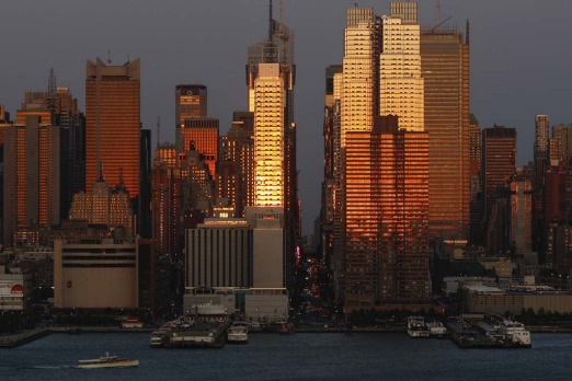 The setting sun reflects off the buildings of Manhattan at sunset on 31 May 2009.