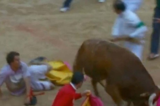 The Australian tourist hurt in the bull run lies on the ground as the heavy beast looms.