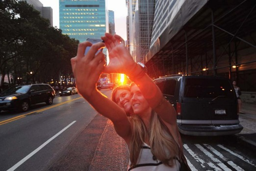 Two women photograph themselves during the Manhattanhenge sunset.