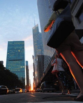 People photograph the sunset during Manhattanhenge.