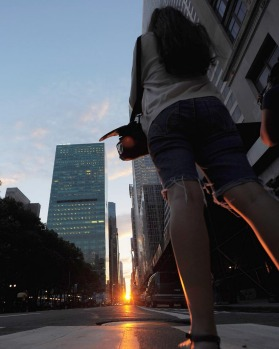 A woman photographs the rare sight of the setting sun during Manhattanhenge 2011.