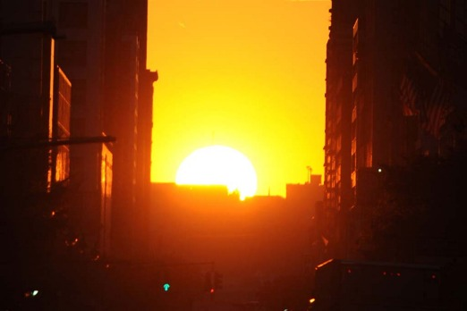 The sun sets along 34th Street, aligning with the Manhattan street grid.
