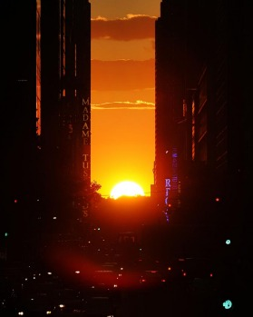 The sun sets on the horizon overlooking 42nd street.