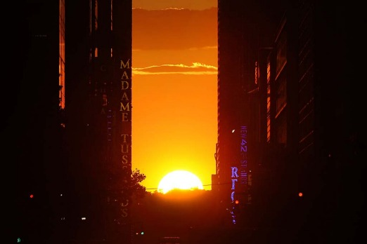 The sun sets on the horizon across 42nd street.