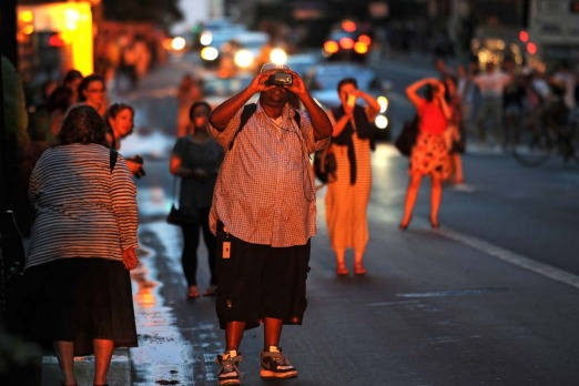 People are bathed in light as they step out into the street to photograph the rare sight.