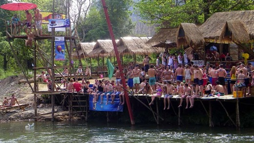 Tourists crowd a riverside bar, by one of the towers used for leaping into the river.