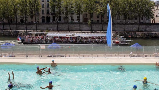 "A tourism boat, called in French ""Bateau mouche"", on the Seine river in front of people swimming in a pool installed on ..."