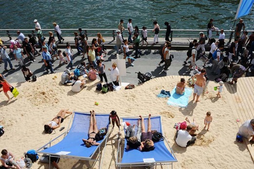 "People walk on the Seine river banks past other people laying on deckchairs and sand during the ""Paris Plage"" yearly event."