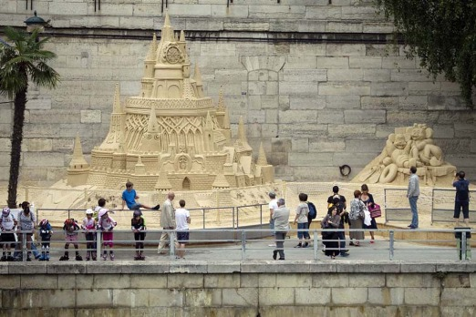 "People look at a sand castle along the River Seine during the ""Paris Plage"" yearly event."
