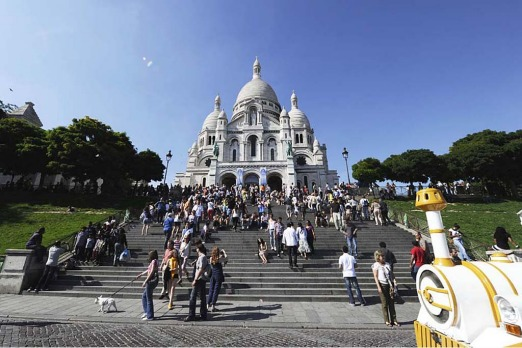 Tourists climb stairs in front of the Sacred Heart (Sacre Coeur) Basilica of Montmartre.