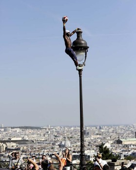 A street performer does acrobatics tricks with a soccer ball as he balances on an old style street light in Paris at the ...