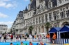 Children play on paddle boats in front of Paris city hall.