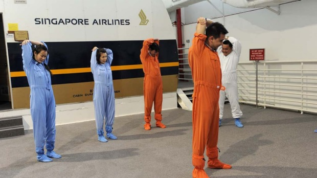 Singapore Airlines cabin crew warm up before performing a land evacuation exercise from a mock-up plane.