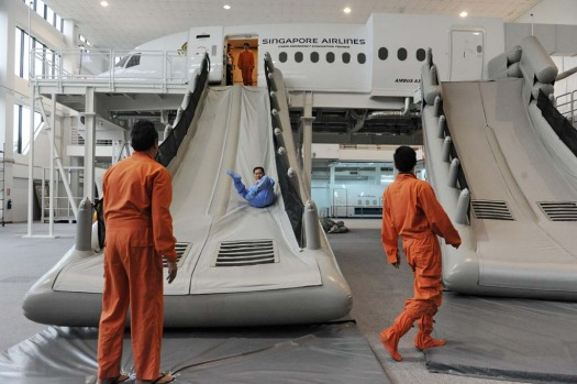 Singapore Airlines cabin crew perform a land evacuation exercise from a mock-up plane as part of their safety training.