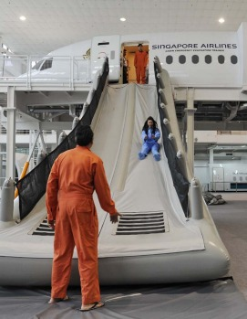 Singapore Airlines cabin crew perform a land evacuation exercise from a mock-up plane.