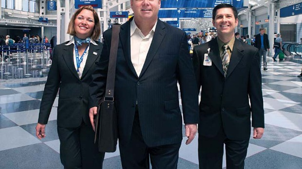Tom Stuker, centre, the first customer ever to fly 10 million miles with United Airlines, walks through Chicago O'Hare ...