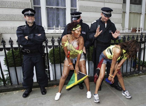 Performers dance in front of police offers during the annual Notting Hill Carnival in central London.