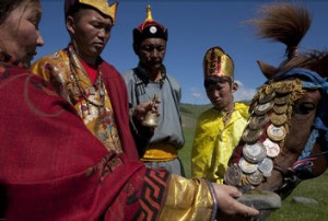 Tribesmen bless a horse before a race in Mongolia.