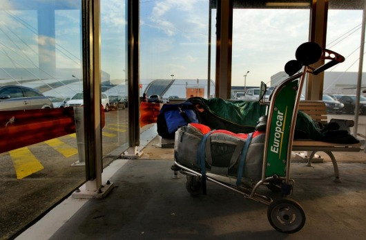 A domestic passenger sleeps on a bench in the carpark with his luggage at the domestic airport during a nationwide ...