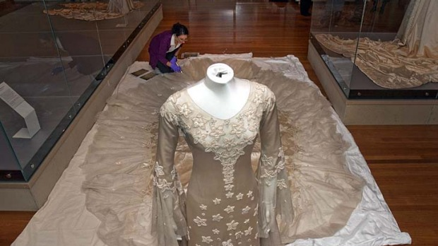 Romantic ... specialist textile installer Keira Millar from the Victorian and Albert Museum inspects the dress by ...