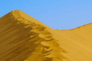 Man on top of sand dune. Photograph by istock. Image can be re-used.  SHD TRAVEL JUNE 7 INSIDER. travel; dune; scenics; ...