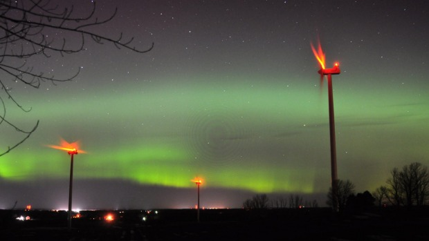 The wind turbines of Consumers Energy's Lake Winds Energy Park operate as the Northern Lights appear over Ludington, ...