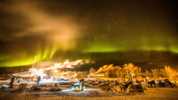 Under the northern lights, Ray Redington Jr arrives in Huslia, Alaska, on March 14, 2015, in the Iditarod Trail Sled Dog ...