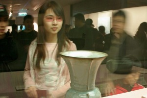 A5ANJW The National Palace Museum in Taipei Girl looking at display of ancient vase and bronze pot. The National Palace ...