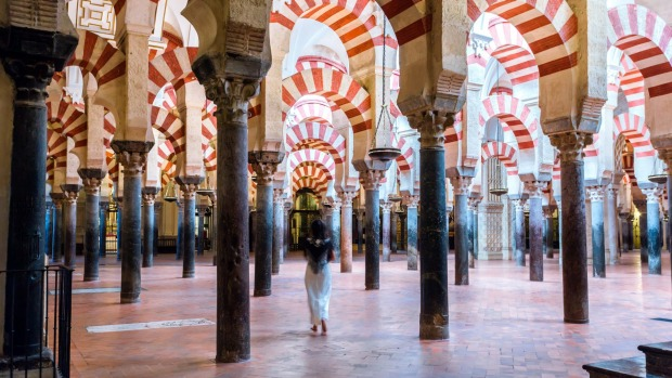 Woman walking inside the Mezquita of Cordoba.