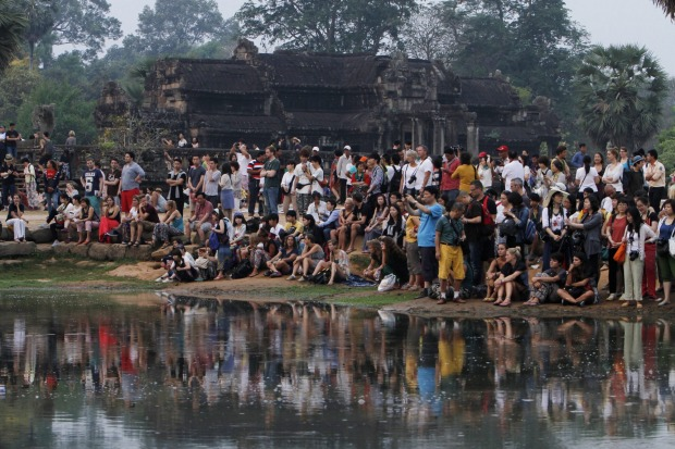 Tourists wait for sunrise at the Angkor Wat at the eastern site of Siem Reap province, some 230 kilometers northwest of ...