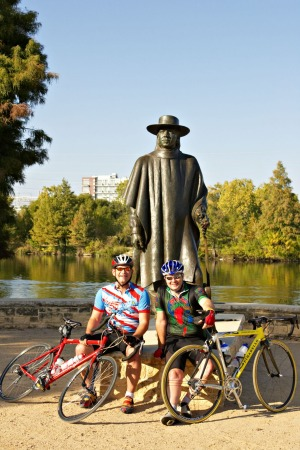 Cyclists rest beneath a sculpture of  famed blues guitarist Stevie Ray Vaughan.