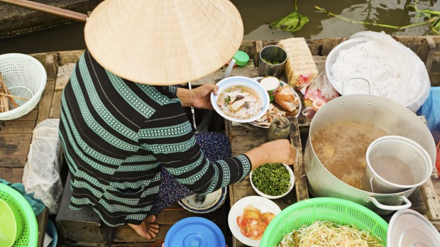 A woman sells pho from her boat in the Mekong river delta, Vietnam.