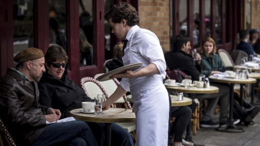 A waiter serves patrons at a restaurant near Rittenhouse Square in Philadelphia, Pennsylvania, US.