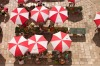 An aerial view of the local farmer's market (Sanitat) in Dubrovnik. The produce is all displayed on tables under the red ...