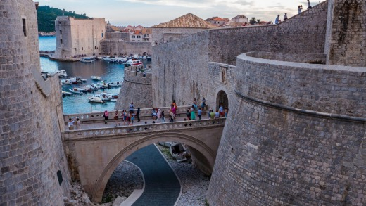 People walking across a small bridge to visit Dubrovnik city walls.