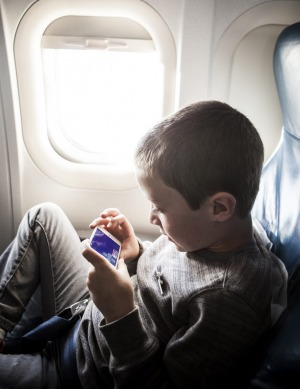 Boy (8yrs) using smartphone on airplane