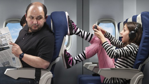 Flying tips. A carefree young girl annoying the passenger infront by pushing his seat. str12cover