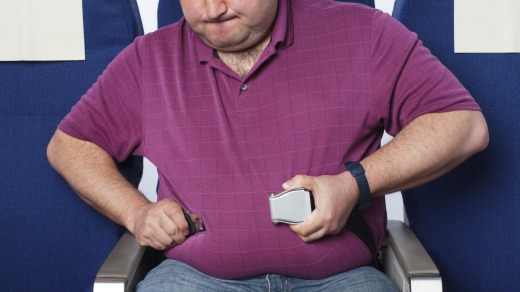 Flying tips. Frustrated overweight man in an airplane trying to close his short seat belt str12cover