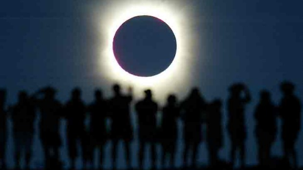 Tourists watch the sun being blocked by the moon during a solar eclipse in the Australian outback town of Lyndhurst, ...
