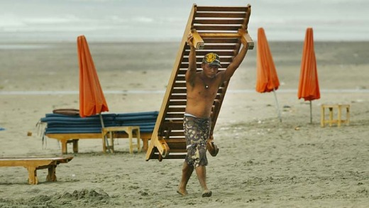 Tourist hot spot ... a man removes a  beach lounger from Kuta Beach.