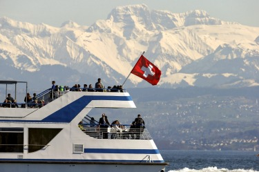 People enjoy the sunny spring weather aboard a tourist vessel sailing in front of the eastern Swiss Alps on Lake Zurich.