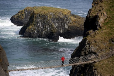 A tourist makes his way across Carrick-a-Rede Rope Bridge on the Causeway coast, north of Belfast. The bridge is ...